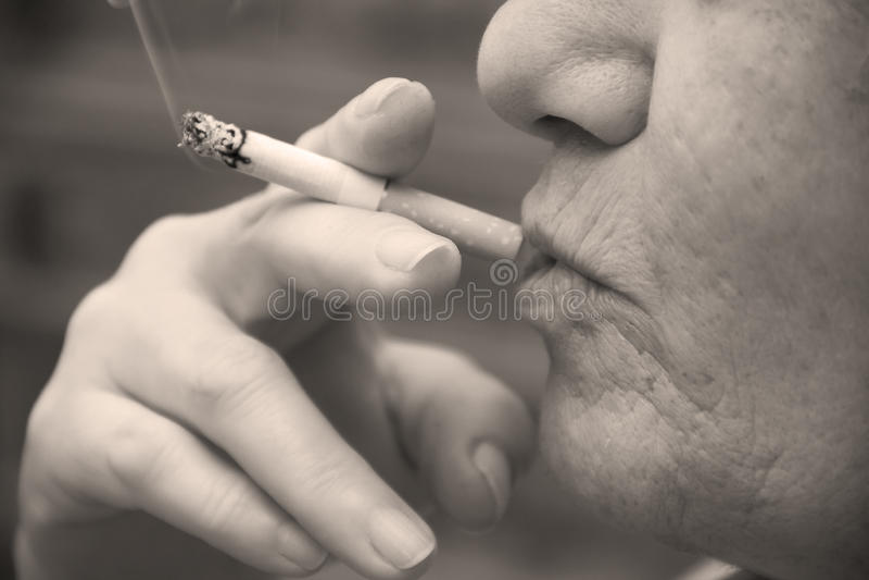 La donna sta fumando una sigaretta immagine stock libera da diritti