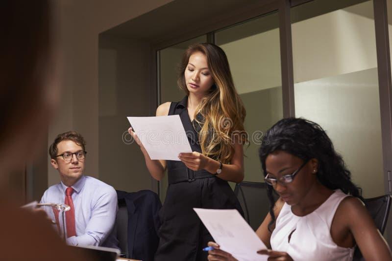 La donna sta il documento della lettura ad una riunione d'affari di sera fotografia stock