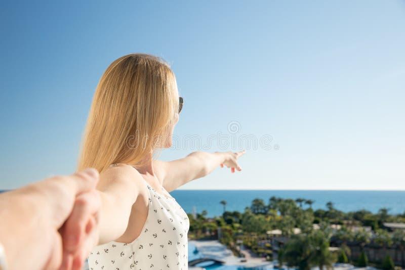 La donna sta indicando con il suo dito il mare da un balkony nella vacanza estiva fotografia stock