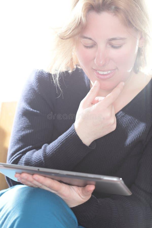 La donna sta leggendo sul computer fotografia stock
