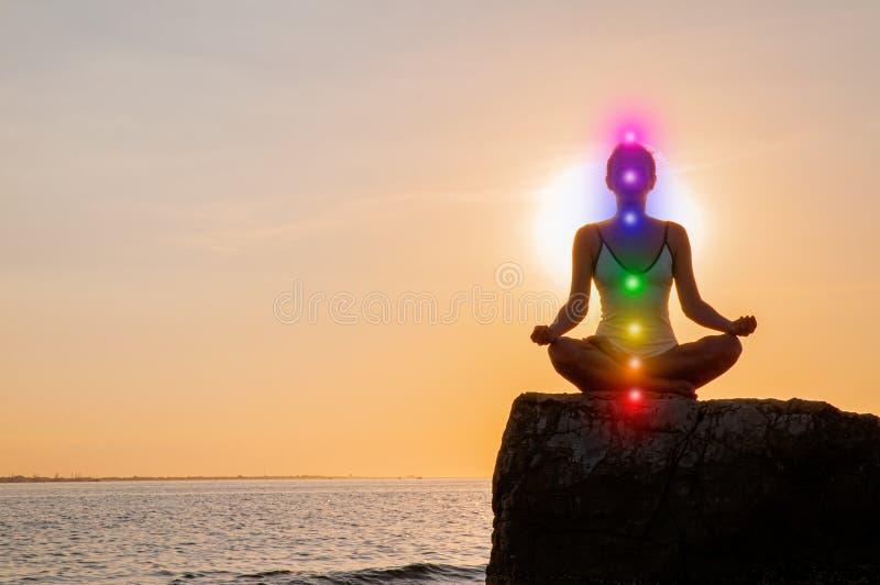 La donna sta meditando con l'ardore sette chakras su pietra al tramonto La siluetta della donna sta praticando l'yoga sulla spiag fotografie stock libere da diritti