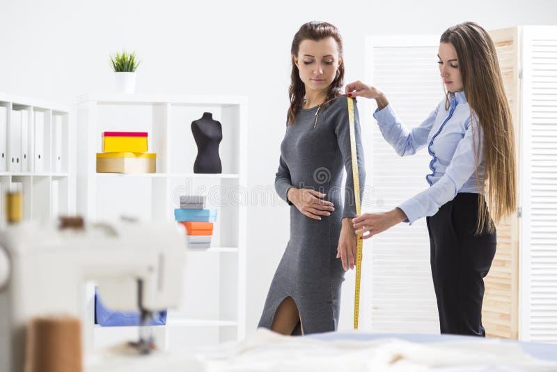 La donna sta misurando il suo braccio del ` s del cliente fotografia stock libera da diritti