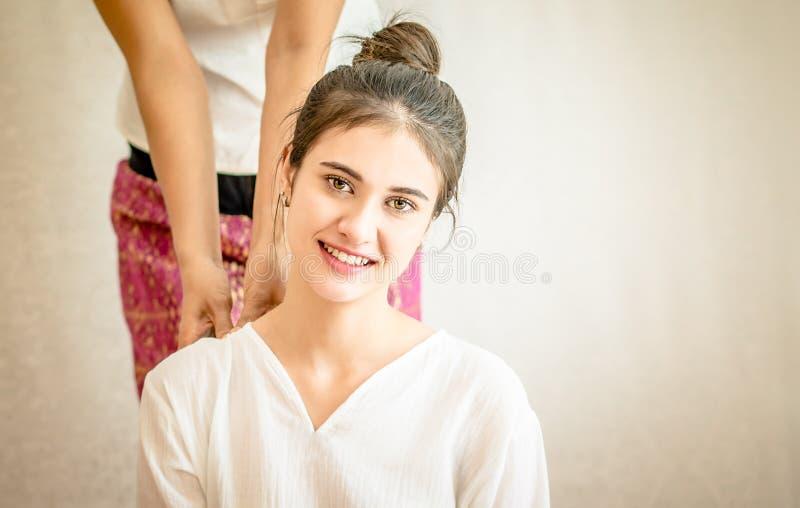 La donna sta ottenendo la stampa tailandese di massaggio della spalla con lo spazio della copia fotografia stock libera da diritti