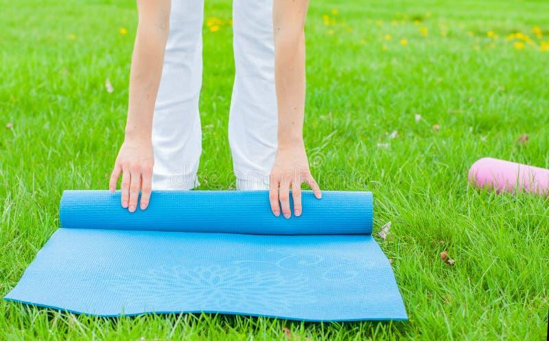 La donna sta piegando la stuoia di forma fisica o di yoga sull'erba La vita sana, tiene i concetti adatti fotografia stock libera da diritti