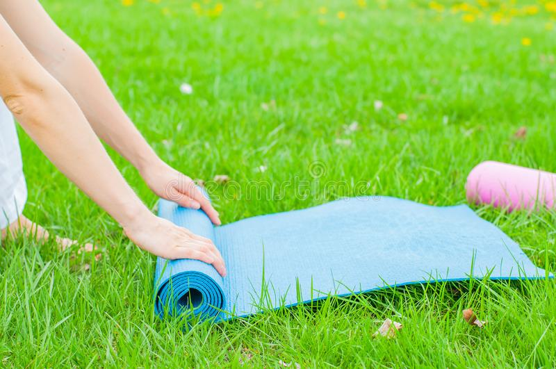 La donna sta piegando la stuoia di forma fisica o di yoga sull'erba La vita sana, tiene i concetti adatti fotografia stock