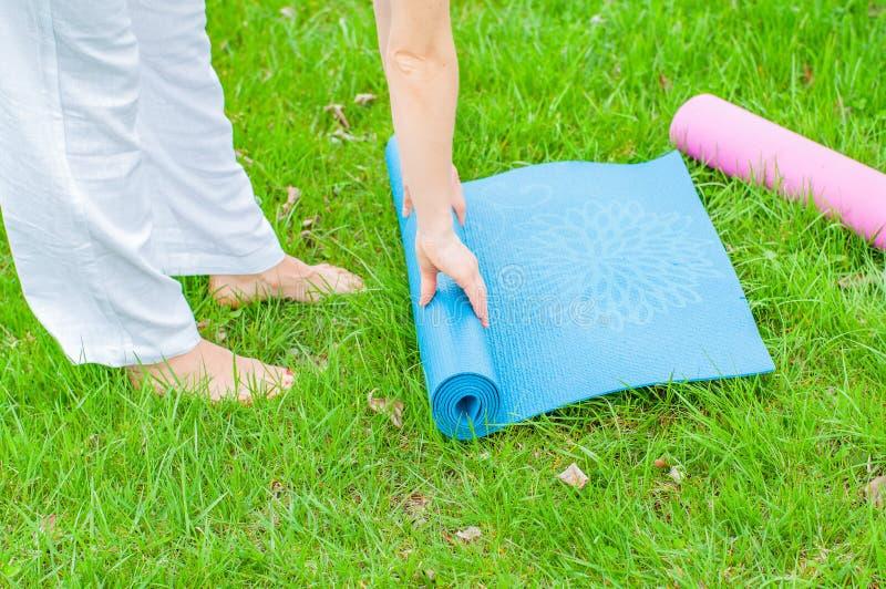 La donna sta piegando la stuoia di forma fisica o di yoga sull'erba La vita sana, tiene i concetti adatti immagini stock libere da diritti