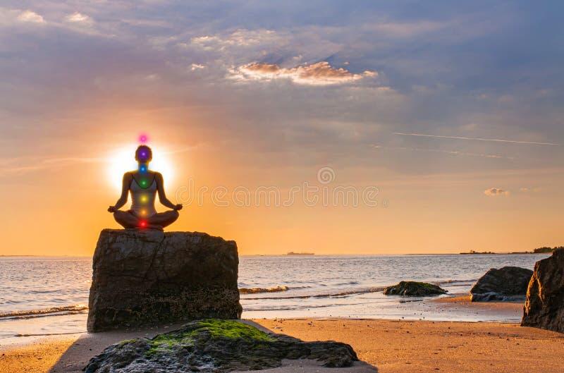 La donna sta praticando l'yoga che si siede sulla pietra nella posa di Lotus al tramonto Siluetta della donna che medita su spiag fotografia stock