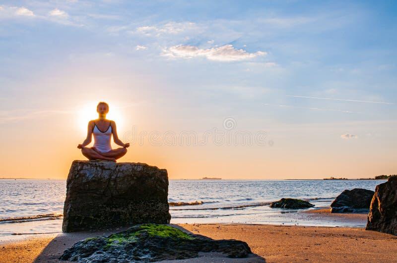 La donna sta praticando l'yoga che si siede sulla pietra nella posa di Lotus al tramonto Siluetta della donna che medita su spiag fotografie stock libere da diritti