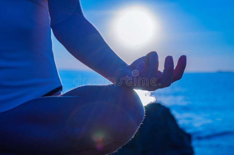 La donna sta praticando la seduta di yoga nella posa di Lotus all'alba Siluetta della donna che medita su spiaggia fotografia stock