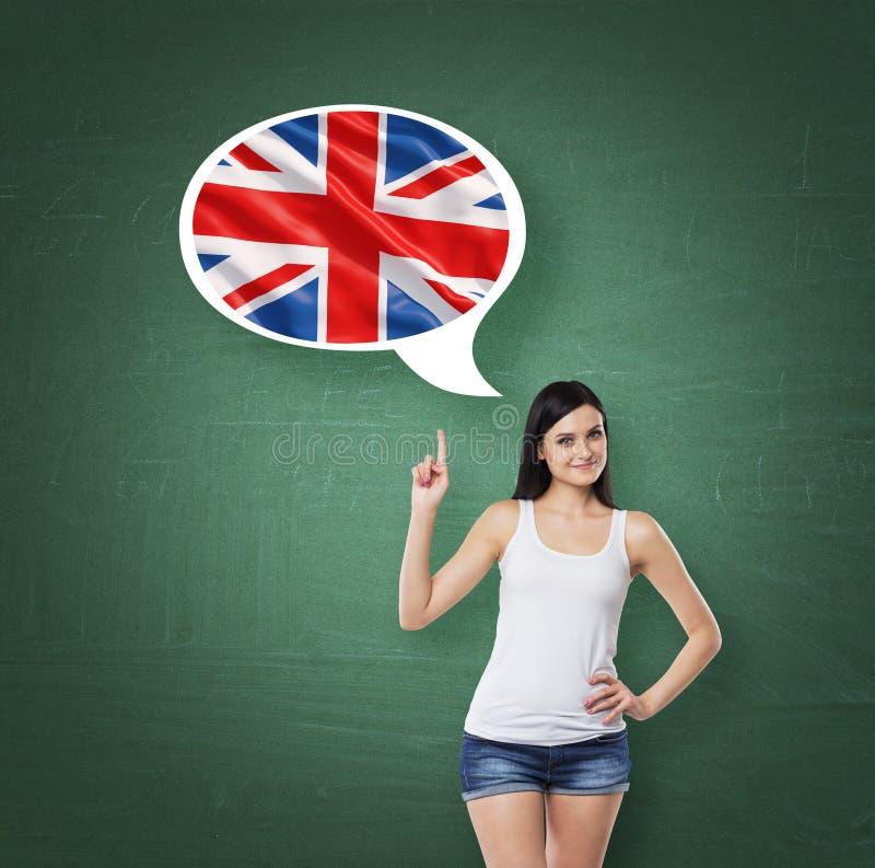 La donna sta precisando la bolla di pensiero con la bandiera della Gran Bretagna Fondo verde del bordo di gesso immagini stock libere da diritti