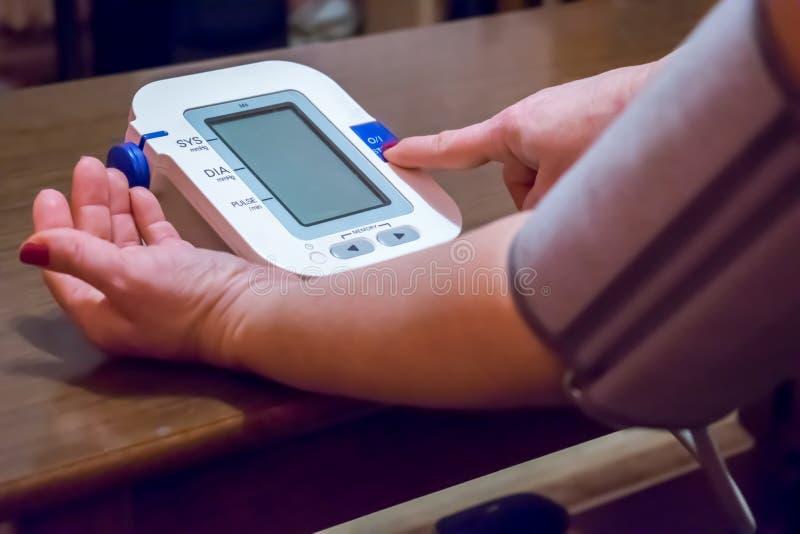 La donna sta prendendo la cura per salute con il monitor e il blo del battito del focolare fotografie stock libere da diritti