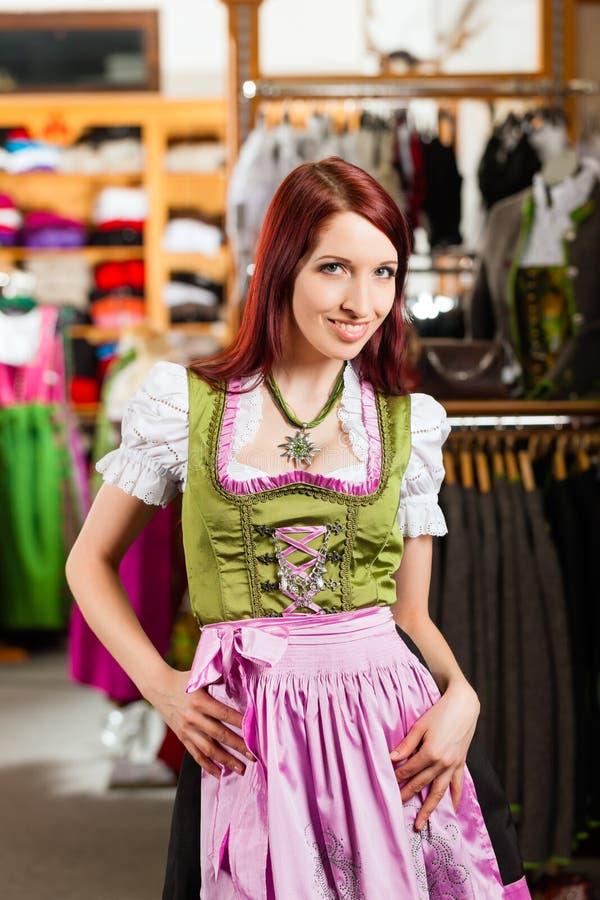 La donna sta provando Tracht o il dirndl in un negozio fotografie stock