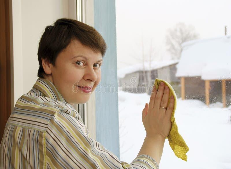 La donna sta pulendo una finestra immagini stock libere da diritti