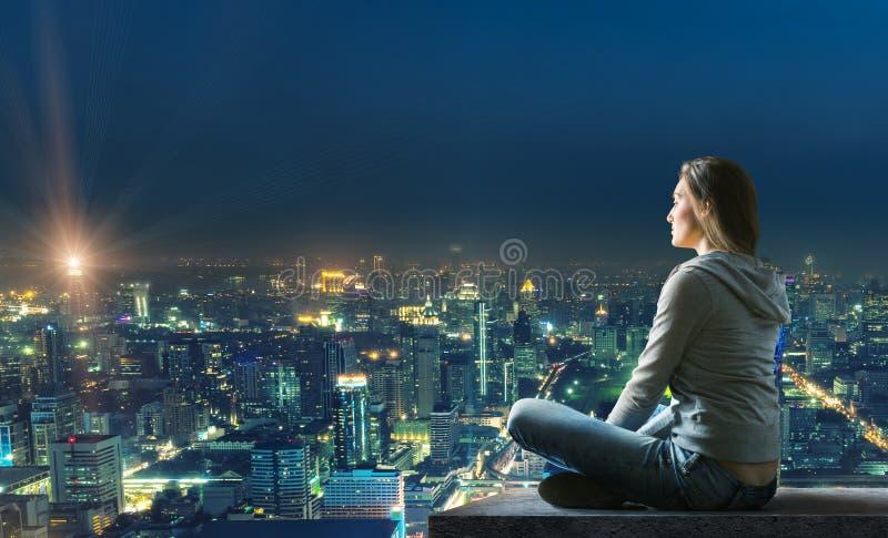 La donna sta sedendosi sopra la città fotografie stock