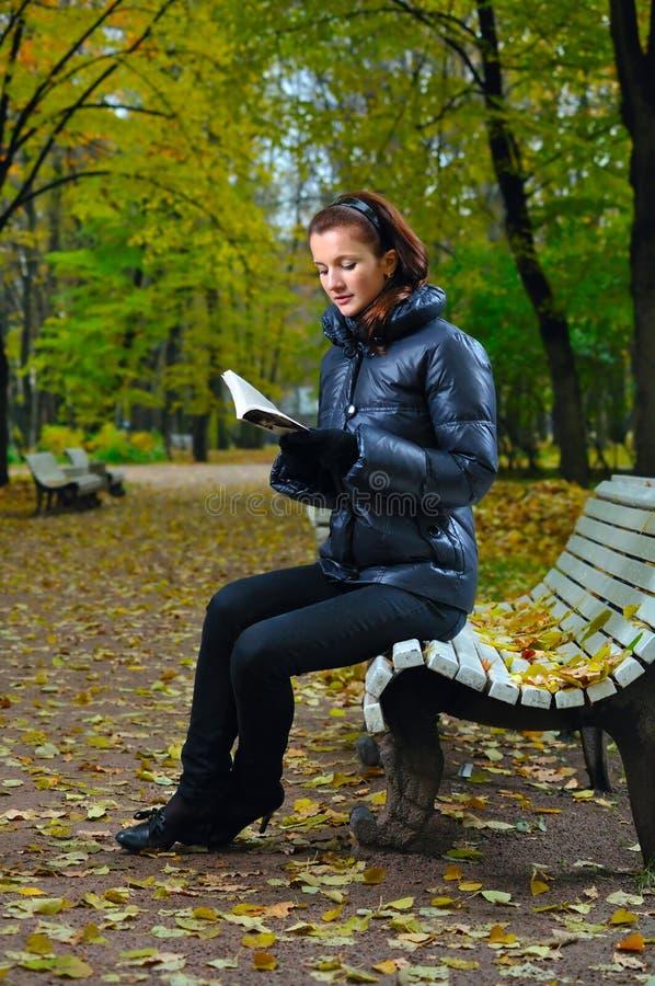 La donna sta sedendosi su un banco e su una lettura fotografia stock
