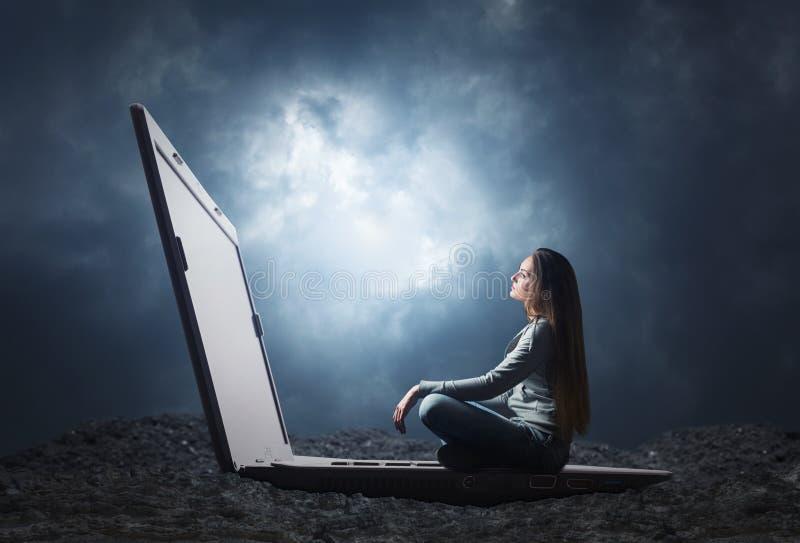 La donna sta sedendosi su un grande computer portatile immagini stock libere da diritti