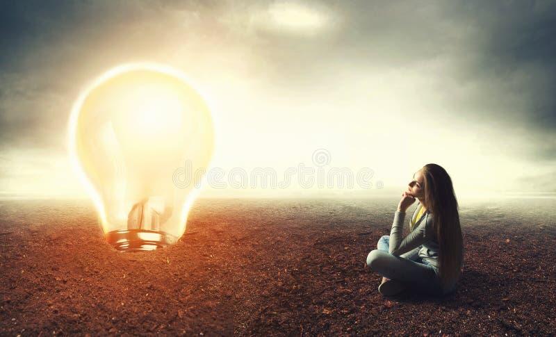 La donna sta sedendosi su una terra e sta esaminando la lampada fotografie stock