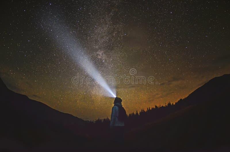 La donna sta stando nella foresta e sta indicando la Via Lattea immagini stock