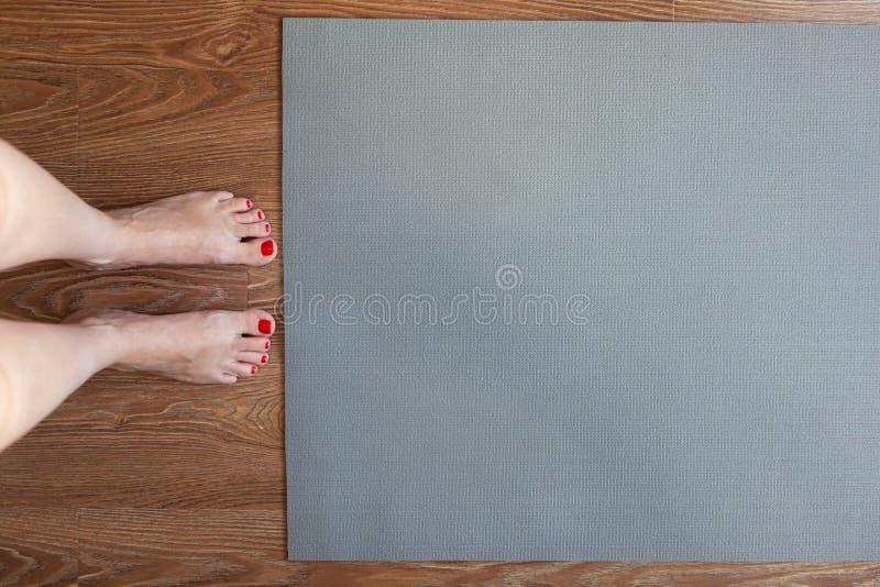 La donna sta stando a piedi nudi sul pavimento davanti alla stuoia relativa alla ginnastica, lei sta andando fare il complesso di fotografia stock