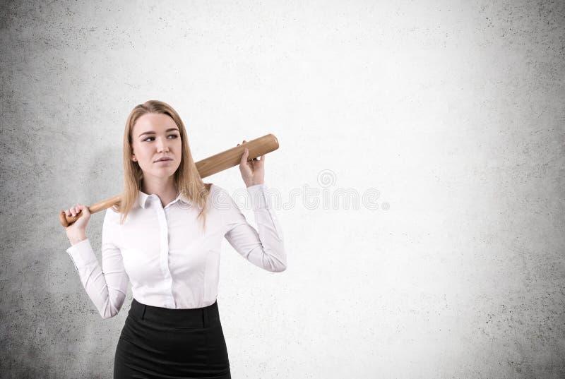 La donna sta stando vicino ad un muro di cemento con la sua mazza da baseball fotografia stock
