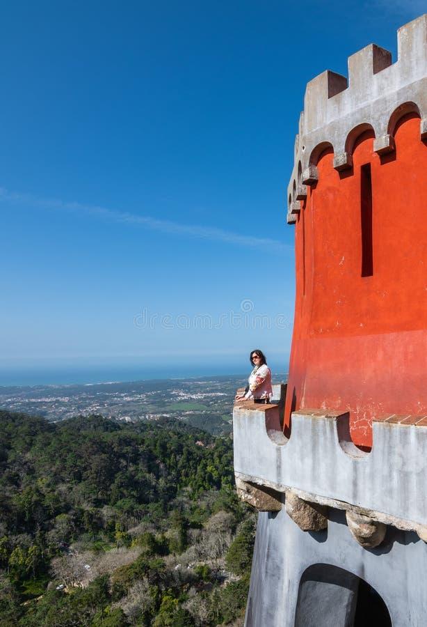 La donna sta su un'alta piattaforma di osservazione del castello contro le montagne fotografie stock libere da diritti