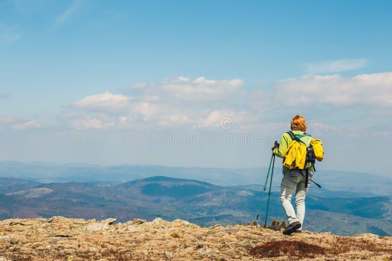 La donna sta sul percorso ed esamina le cime immagini stock