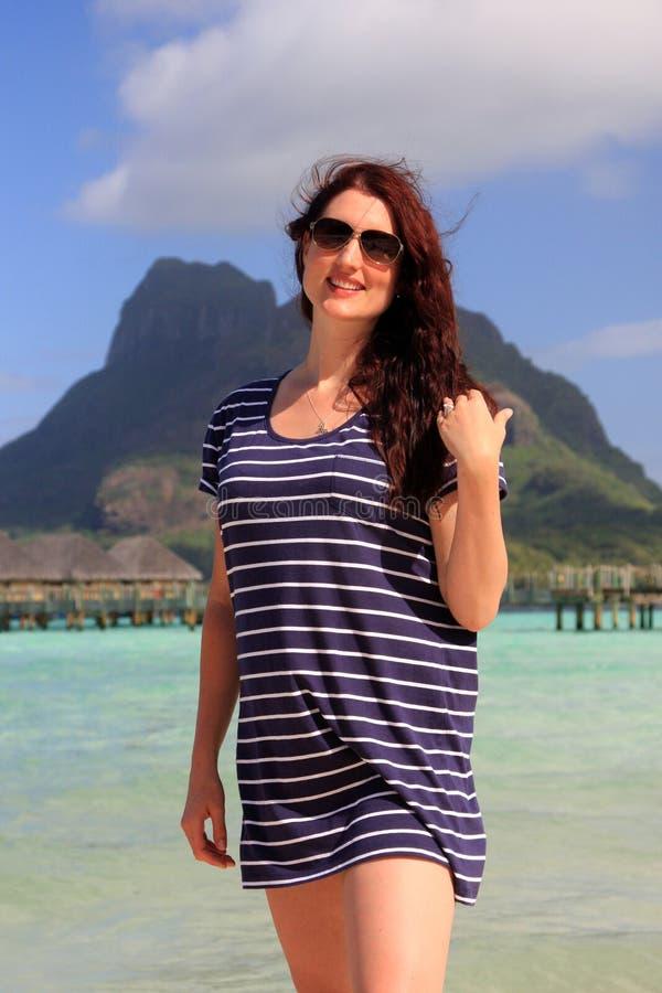 La donna sta sulla spiaggia della località di soggiorno tropicale fotografia stock libera da diritti