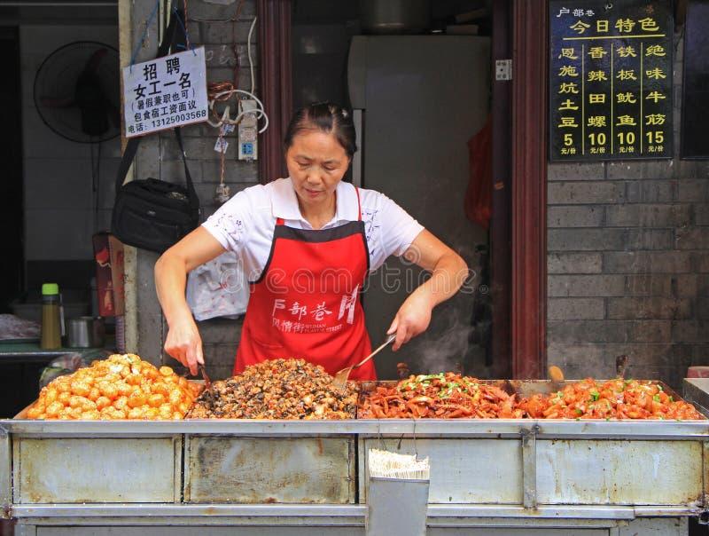 La donna sta vendendo gli spuntini all'aperto a Wuhan, Cina fotografie stock libere da diritti
