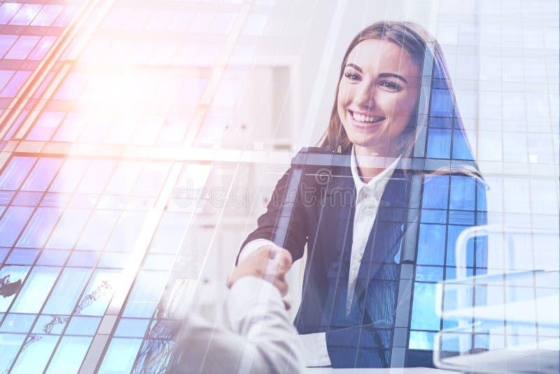 La donna stringe le mani in ufficio, grattacielo immagini stock libere da diritti