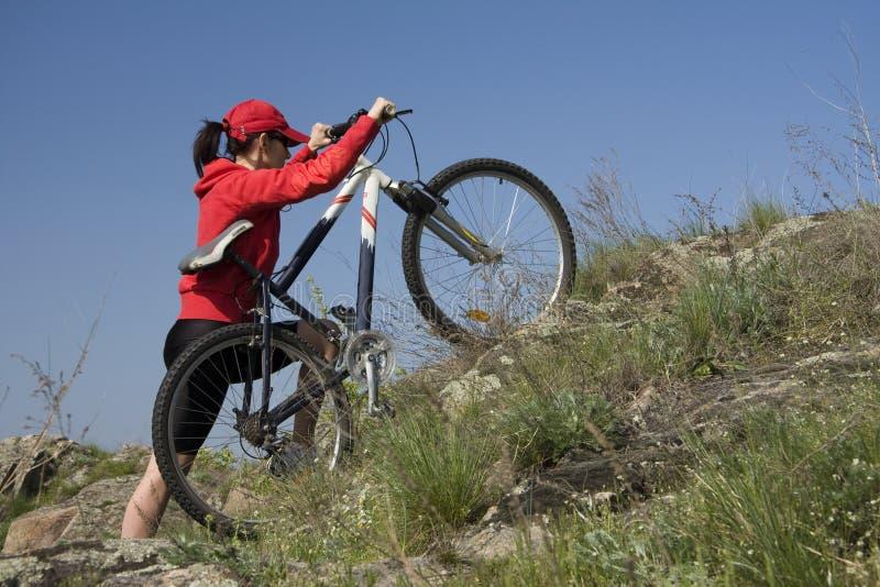 La donna su una bicicletta della montagna fotografia stock libera da diritti