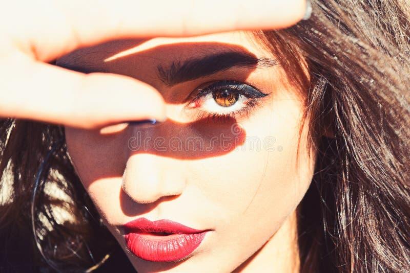 La donna sul fronte calmo con trucco, riguarda la luce solare di mano, defocused Signora sembra attraente, fine su Luce solare lu fotografia stock