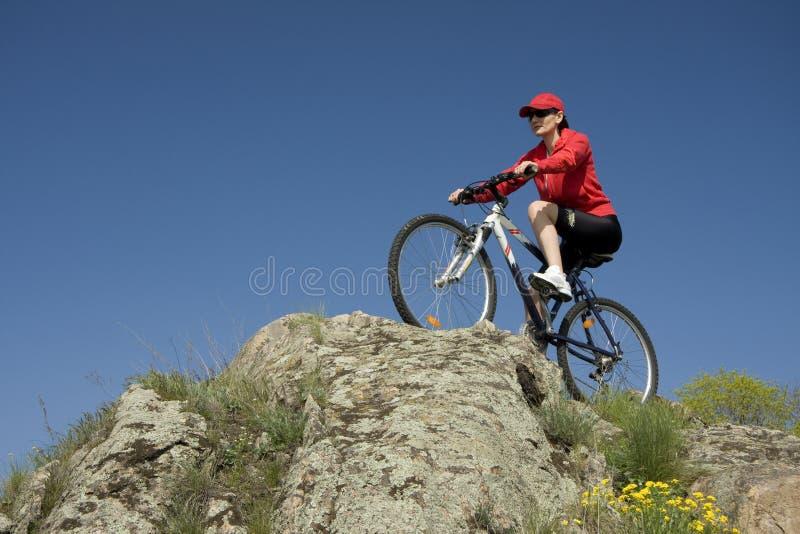 La donna sulla bicicletta della montagna fotografia stock