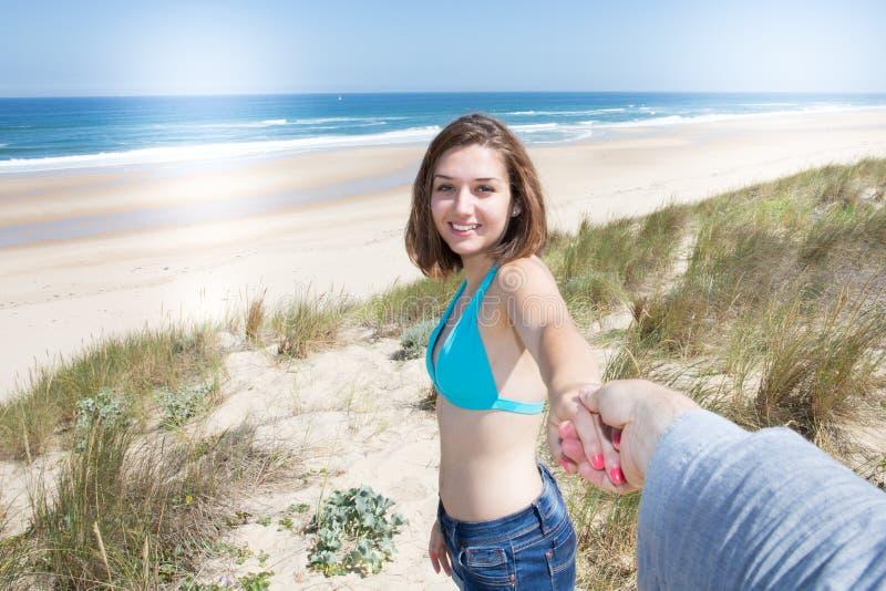 La donna sulla vacanza sulla spiaggia raggiunge fuori al suo ragazzo per andare sulla sabbia del mare immagine stock libera da diritti