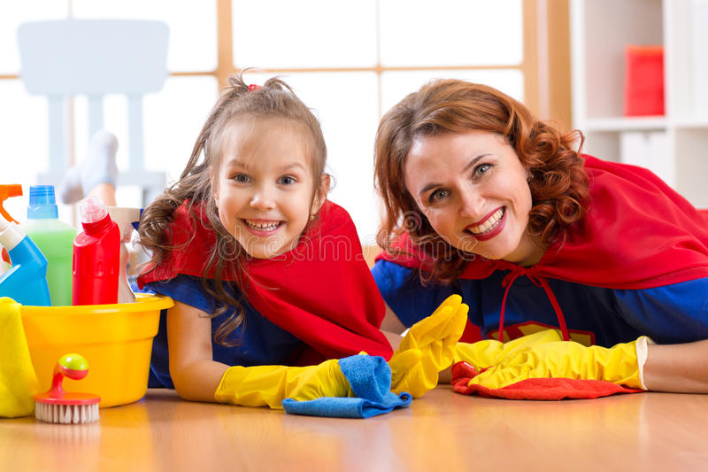 La donna sveglia e sua figlia del bambino si sono vestite come i supereroi che puliscono il pavimento e sorridere immagine stock libera da diritti