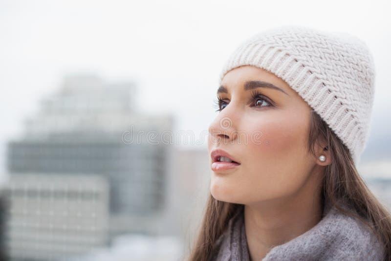 La donna sveglia pensierosa con l'inverno copre sulla posa fotografie stock libere da diritti