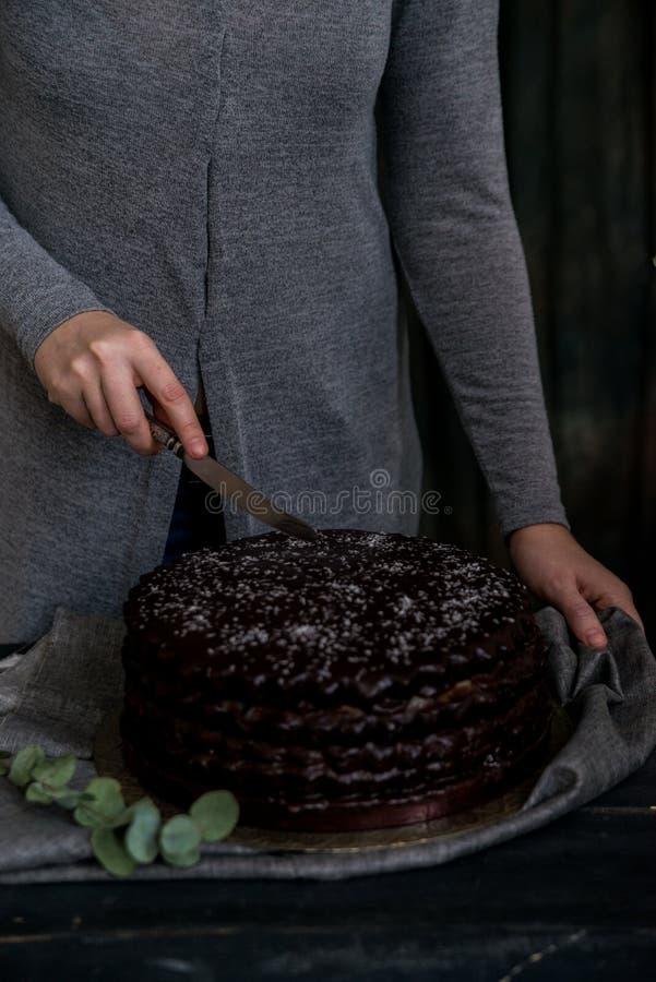 La donna taglia la fine del dolce di cioccolato Toni scuri fotografia stock