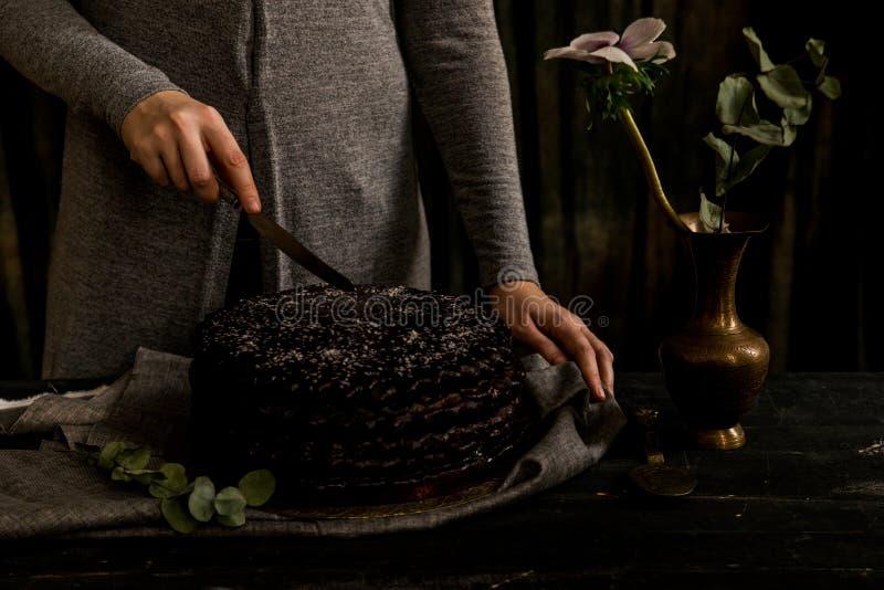 La donna taglia la fine del dolce di cioccolato Toni scuri fotografia stock libera da diritti