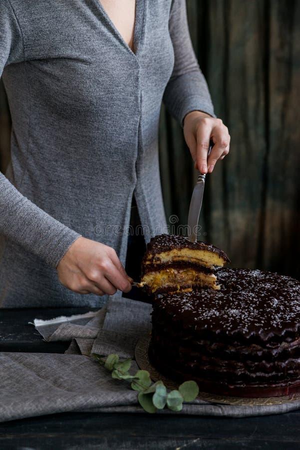 La donna taglia la fine del dolce di cioccolato Toni scuri immagini stock libere da diritti