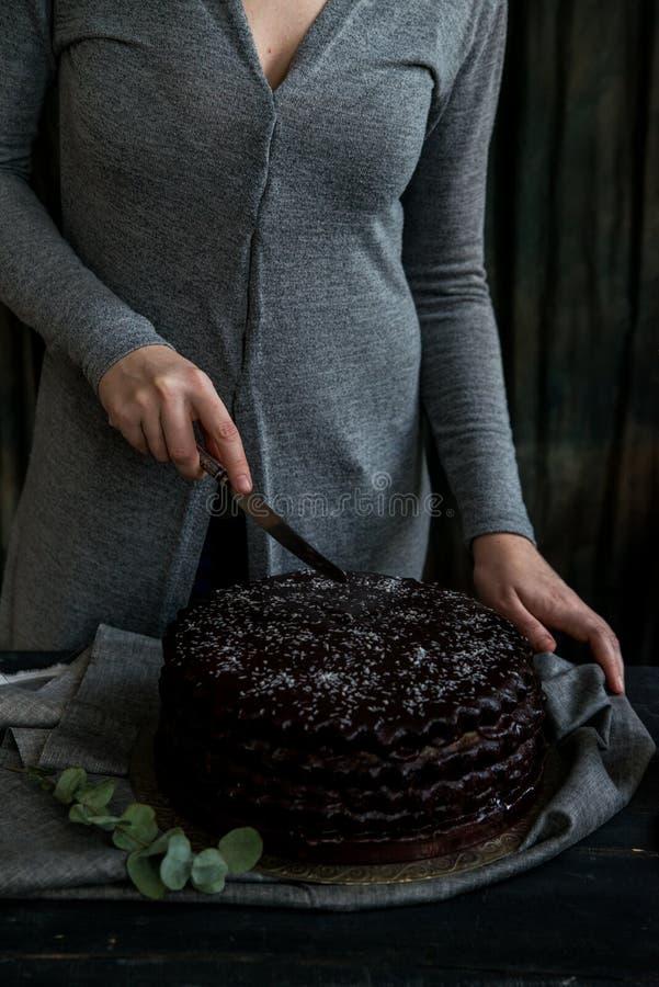 La donna taglia la fine del dolce di cioccolato Toni scuri immagine stock