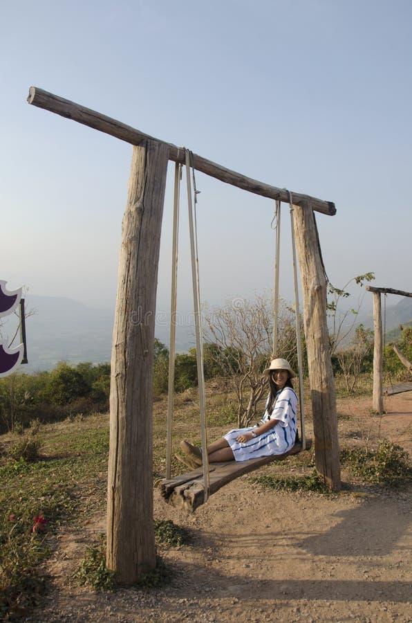 La donna tailandese si siede ed il gioco sul banco di legno oscilla il giocattolo immagini stock libere da diritti