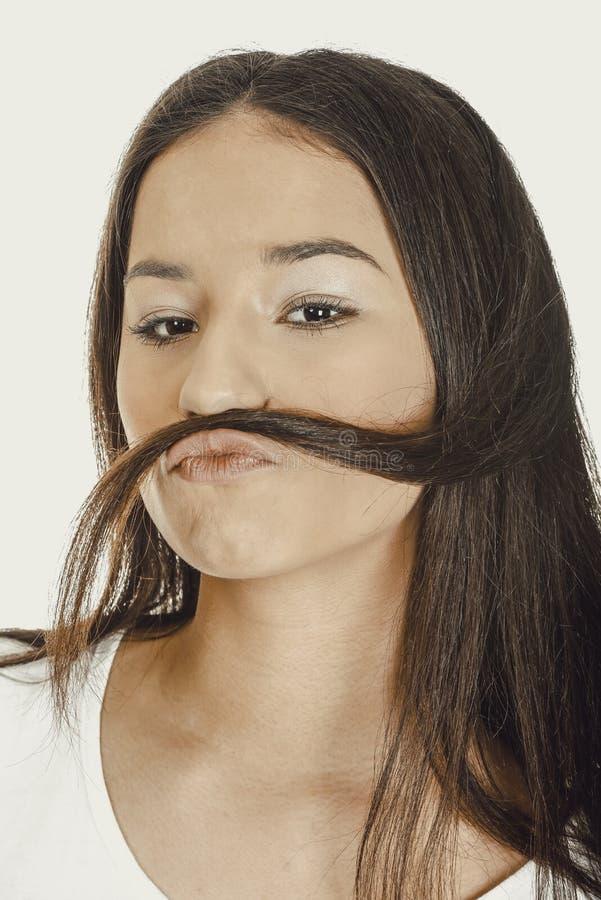 La donna teenager che mette i capelli gradisce i baffi fotografia stock libera da diritti