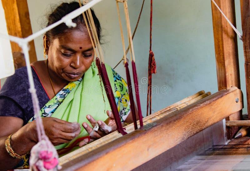 La donna tesse il tessuto su un telaio tradizionale immagini stock