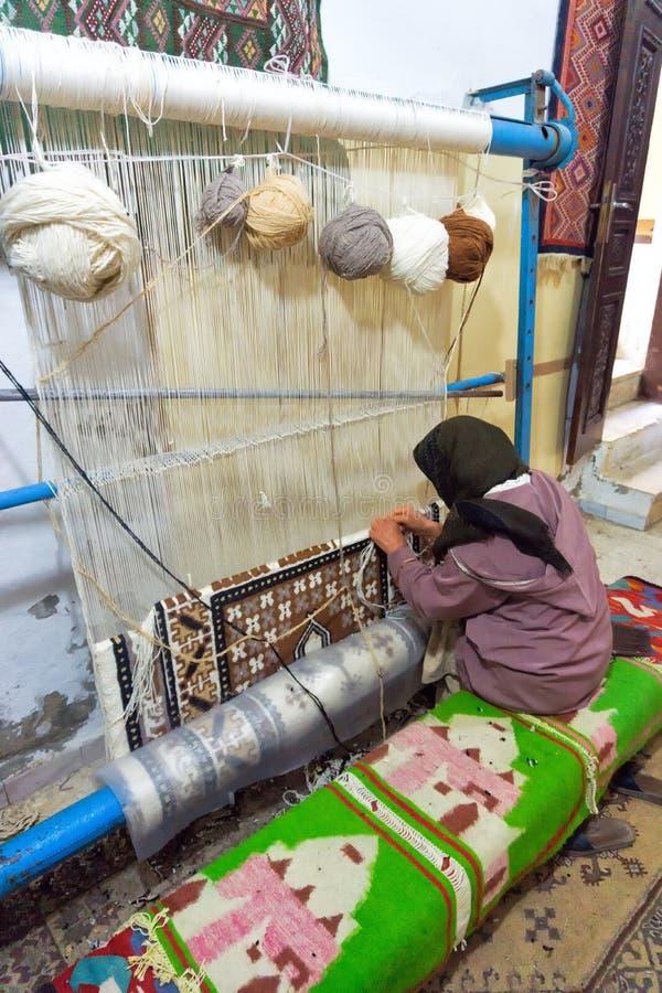 La donna tesse a mano un tappeto in Qayrawan, Tunisia fotografie stock libere da diritti