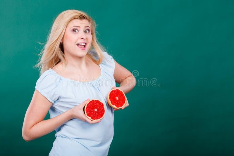 La donna tiene gli agrumi del pompelmo sul seno fotografie stock