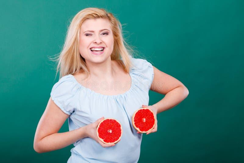 La donna tiene gli agrumi del pompelmo sul seno immagini stock