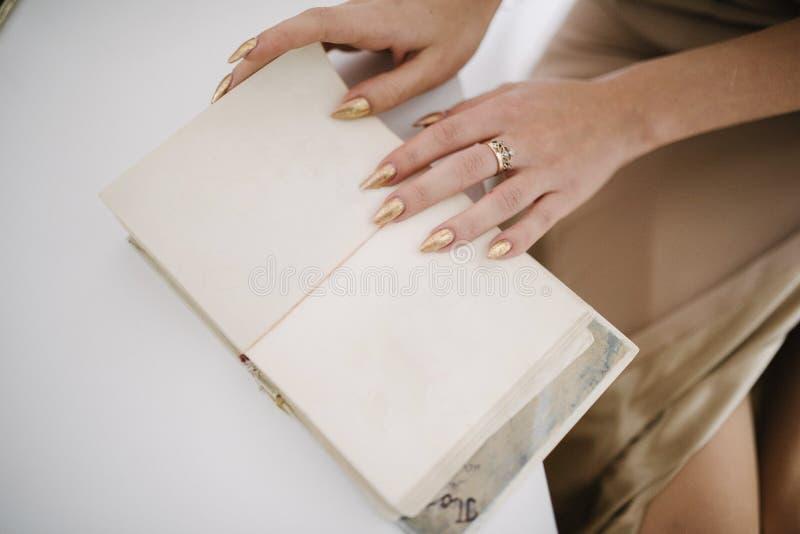 la donna tiene il libro vuoto aperto in sue mani Libro aperto con le pagine vuote nel woman& x27; mani di s immagine stock
