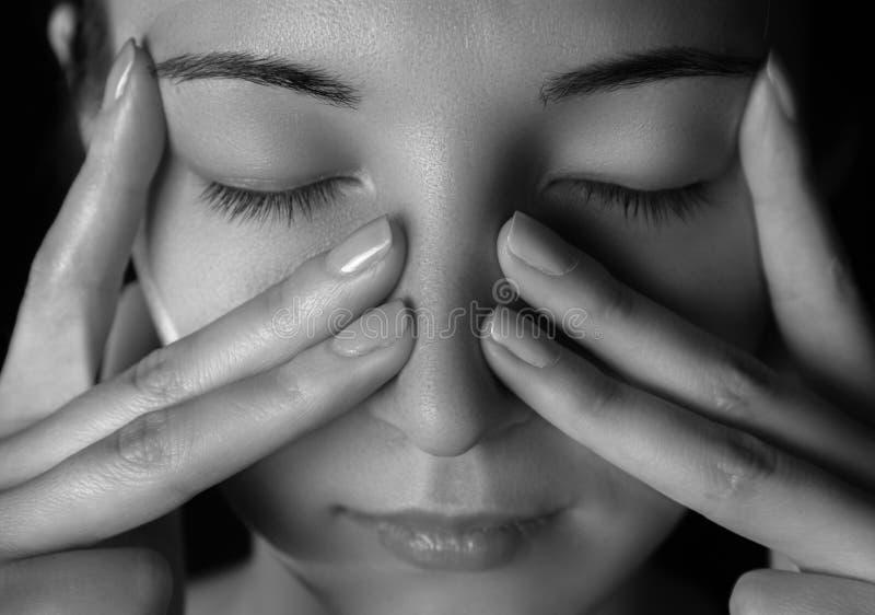 La donna tiene il suo naso fotografie stock libere da diritti