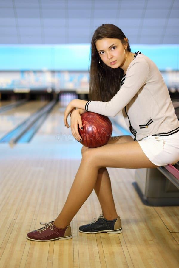 La donna tiene la sfera e si siede nel randello di bowling immagine stock