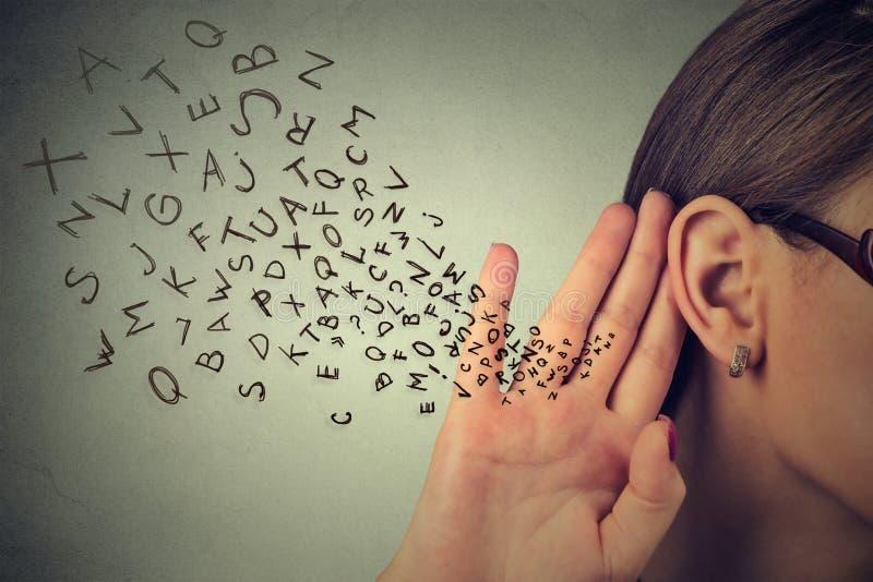 La donna tiene la sua mano vicino all'orecchio ed ascolta con attenzione fotografia stock libera da diritti