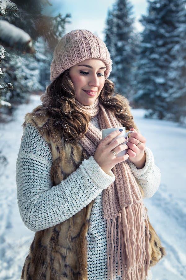 La donna tiene la tazza di caffè con la caramella gommosa e molle fotografie stock